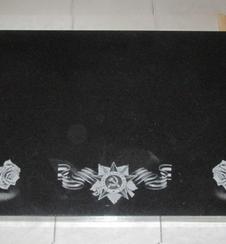 Общая картина гранитного памятника с изображением свечей и роз по нижним углам, георгиевская ленточка с орденом